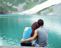 Young adults lovers looking at pristine aqua mountain lake photo of adult color with snow and woods in background Royalty Free Stock Photography