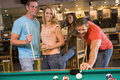 Young adults playing pool in a bar Royalty Free Stock Photography
