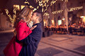 Young affectionate couple kissing tenderly on christmas street Stock Photos