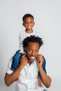 A Young African American Boy Sits Atop the Shoulders of His Dad Royalty Free Stock Photo
