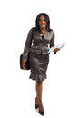 Young african american businesswoman holding folders isolated on white background walking Stock Photo