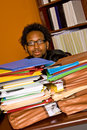 Young african american male buried work looks over stacks colorful folders piled top his desk Royalty Free Stock Photos