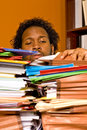 Young african american male buried work looks two stacks colorful folders piled top his desk Royalty Free Stock Images