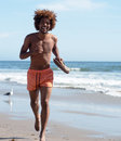 Young african american male running on beach Royalty Free Stock Image
