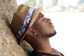 Young african american man with hat relaxing outdoors Royalty Free Stock Photo