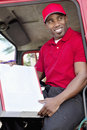 Young African American man sitting in delivery truck with box Royalty Free Stock Image