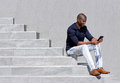 Young african american man sitting on steps using tablet Royalty Free Stock Photo