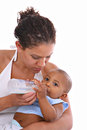 Young african american mother feeding baby boy with milk bottle Royalty Free Stock Photos