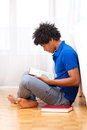 Young african american student reading books african people seated on the floor Stock Photos