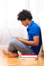 Young african american student using a laptop african people seated on the floor Stock Photo