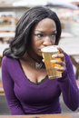 Young african american woman drinks pale ale pint glass Stock Photos