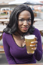Young african american woman drinks a pale ale from a pint glass Royalty Free Stock Image
