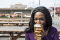 Young african american woman drinks a pale ale from a pint glass Stock Photo