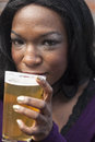 Young african american woman drinks a pale ale from a pint glass Royalty Free Stock Photo