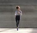 Young african american woman jogging alone outdoors Royalty Free Stock Photo