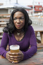 Young african american woman and a pint of pale ale Stock Photo