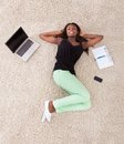 Young african american woman relaxing on rug at home high angle view of Royalty Free Stock Photo