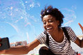 Young african american woman talking selfie outdoors with big soap bubbles Royalty Free Stock Photo