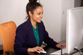 Young african business woman working at her office portrait of happy sitting desk and on desktop computer Stock Photography