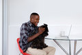 Young african guy playing with his pet dog Royalty Free Stock Photo