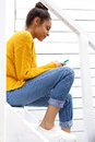 Young african lady sitting on stairs using cellphone Royalty Free Stock Photo