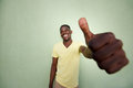 Young african man gesturing thumbs up sign by green wall Royalty Free Stock Photo