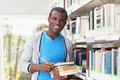 Young african man smiling in library Royalty Free Stock Image