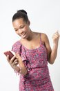 Young african woman excited over text message black female a chat Royalty Free Stock Image