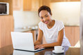 Young african woman kitchen pretty in her using laptop computer Stock Photo