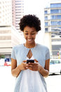 Young african woman listening to music on the mobile phone portrait of wearing earphones Stock Image