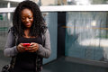 Young african woman sending an sms on her mobile smiling as she types in the text with thumbs the touch screen Royalty Free Stock Image