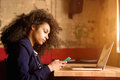 Young african woman sitting in a cafe using mobile phone Royalty Free Stock Photo