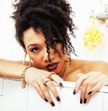 Young afro-american teen girl laying in bath with foam, wearing Royalty Free Stock Photo