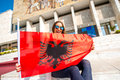 Young albanian patriot woman with flag sitting in front of national museum in tirana city Royalty Free Stock Image