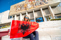 Young albanian patriot woman with flag sitting in front of national museum in tirana city Royalty Free Stock Photo