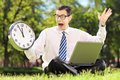 Young angry businessperson with computer sitting on grass and lo looking at clock in a park Royalty Free Stock Photography