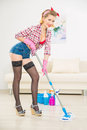 Young appealing woman mopping the floor thoroughly is holding a mop and cleaning Stock Photo