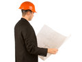Young architect studying a building blueprint as he stands sideways to the camera in his suit and hardhat isolated on white Royalty Free Stock Photography