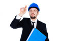 Young architect working on a virtual interface or structural engineer in hardhat and suit raising his finger and pointing as Royalty Free Stock Photos
