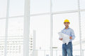 Young architect in yellow hard hat with blueprint in office portrait of a a bright Stock Images