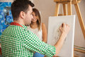 Young artist drawing a portrait rear view of male working on of pretty female model in his studio Royalty Free Stock Image