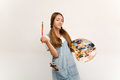 Young artist holding a brush to paint and palette. Royalty Free Stock Photo