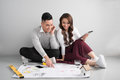 Young asian adult couple sitting on flor planning new home desig Royalty Free Stock Photo