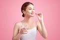 Young asian beauty young woman eating pills and drinking water o Royalty Free Stock Photo