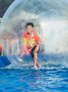 Young asian boy playing inside a floating water walking ball very happy Stock Photo