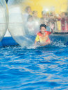 Young asian boy playing inside a floating water walking ball very happy Stock Image