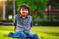 Young asian boy sits on the green grass in summer park Royalty Free Stock Photos