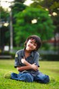Young asian boy sits on the green grass in summer park Royalty Free Stock Photo