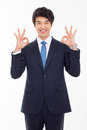 Young asian business man showing okay sign isolated on white background Royalty Free Stock Photography