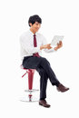 Young asian business man using pad pc sitting chair isolated white background Royalty Free Stock Image